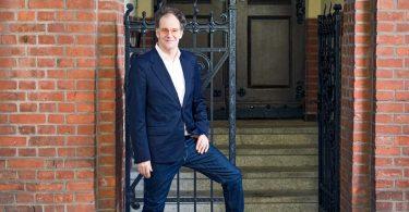 Kabarettist Chin Meyer vor einer Hauswand